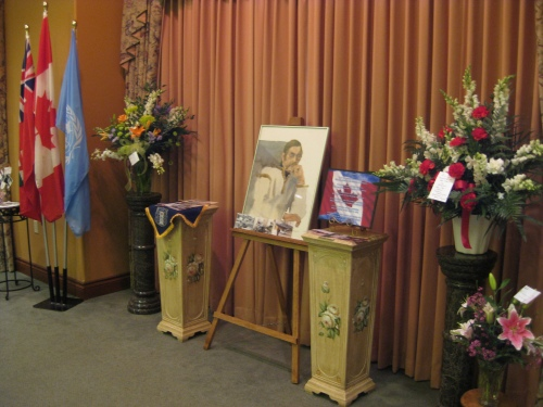 """The set-up at Tom Bjarnason's funeral service in Windsor on August 31. The painting is an original portrait of """"Bjarni"""" that his pal Tom McNeely, another renowned Canadian illustrator, did in the 1970s. Bjarni was honoured and hailed this day by his family -- dozens of fabulous nieces and nephews of various generations. The Royal Canadian Legion - Windsor Veterans Memorial Committee attended to put on a wonderful service with honour guard, Padre Stan Fraser officiating. Tom was ushered out in real class, as was perfectly appropriate. (Larry Milberry)"""