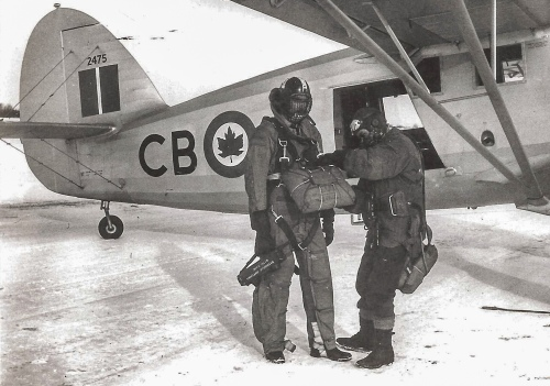 "Para-rescue jumpers check each other out (circa 1947-48) prior to a training jump from Norseman 2475. Sgt William Farr is ensuring that everything is in order with Cpl T.W.L. Dawson's equipment (the RCAF caption describes them as ""mercy jumpers""). Note such early safety features as the helmet with metal-mesh facemask, rugged cloth jump suit, and sturdy gauntlets. Cpl Dawson holds a battery-operated portable radio. For many good reasons, the Norseman was ideal in search and rescue, e.g. note its large cabin doors. (PL39565)"