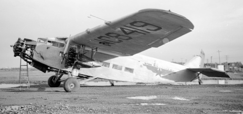 "This magnificent Ford Trimotor NC8419 came though Edmonton one day, perhaps on delivery from ""The Lower 48"" to Alaska's Star Airlines. The Alaska State Archives has a photo of it on skis with Star in 1937, so it might have shown up in Edmonton any time up to 1942, when Star became Alaska Star Airlines. Leslie shot it happily as he saw it -- step ladder and all. Note that the light is long, so it's an early or a late-in-the-day shot (the fuss budgets preferred mid-day lighting). NC8419 was Ford 5-AT-C No.58 built in 1929 for Northwest Airlines of Minneapolis. Research points to a strange story about it. The original plane crashed in 1959 -- years after Leslie saw it. By then it was doing forestry work and went down during fire operations. The data plate was salvaged and used to legitimize the restoration of today's N8419, which is a combination of parts from several Ford wrecks. ""New"" N8419 today flies with the Kalamazoo Aviation History Museum in Michigan."
