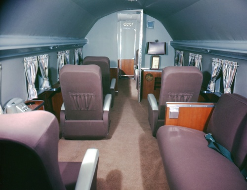 The interior of a typical Canadair VIP DC-3 conversion. Oversized comfy seats were de rigeur. Note the other furnishings of the day -- curtains, telephone, cabinetry, lamp, etc. This view looks aft toward the door into the biffy.