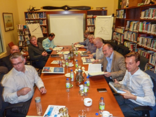 "The CAE people take a break during their meeting in the Vintage Wings library to flip through their copies of ""The CAE Story""."