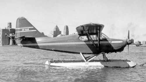 "In November 1945 the historic Stinson Aircraft Co. of Wayne, Michigan introduced its Model 108 Voyageur, priced initially at $5489. In his quintessential study, US Civil Aircraft, Joseph Juptner notes: ""Dealers were having no trouble selling this airplane and by the end of 1946 some 1436 were built and sold"". By 1948 Stinson had turned out more than 5000 in three main models. Then the company also was clobbered by the 1948 slump. Piper swooshed in to buy Stinson, but had no enthusiasm for the 108, so production ended. Happily, hundreds of these lovely postwar ""family planes"" survive all over the US and Canada. Here, Stinson 108-3 CF-HJE, owned by Arcade Electric Co., bobs at its buoy at Toronto Island Airport c1955. Beyond are Toronto's only two skyscrapers of the day – the 32-storey Bank of Commerce on the right, and the Royal York Hotel. Today, these can barely be picked out among the crush of skyscrapers. In 2016 Transport Canada still listed 279 Stinson 108s, CF-HJE included. (Al Martin)"